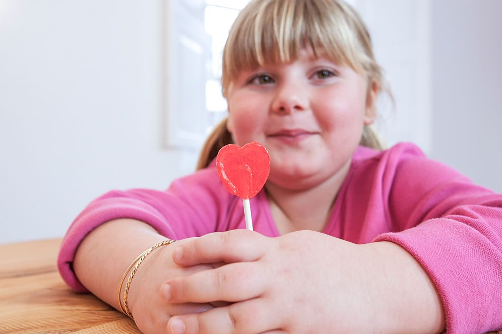 Portrait of overweight girl holding heart shape lollipop