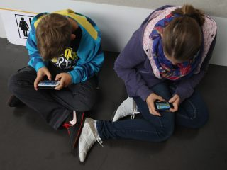 RUESSELSHEIM, GERMANY - SEPTEMBER 22:  Children play video games on smartphones while attending a public event on September 22, 2012 in Ruesselsheim, Germany. Smartphones, with their access to social networks, high-resolution screens, video games and internet acess, have become commonplace among children and teenagers across the globe.  (Photo by Sean Gallup/Getty Images)