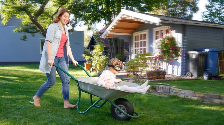 Mother having fun with daughter in wheelbarrow in garden