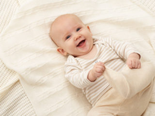 Baby girl (3-6 months) lying on blanket, smiling