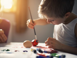 Little boy painting easter eggs at the table. The boy is 6 and his sister is visible in the background. The kids are having fun in sunny room.