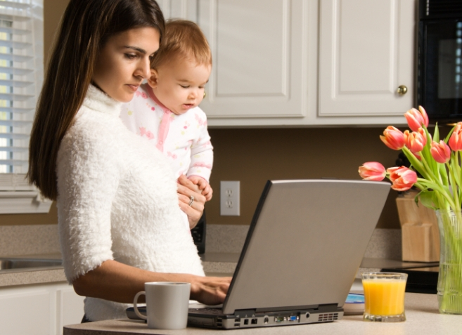 Mother holding baby  and typing on laptop computer in kitchen.
