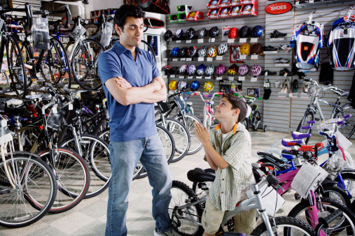 Son begging father for new bike in bike shop