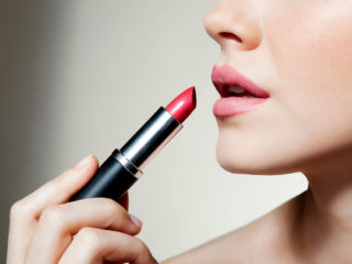 D18TXF Woman applying lipstick