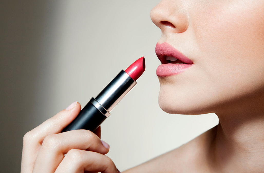 D18TXF Woman applying lipstick