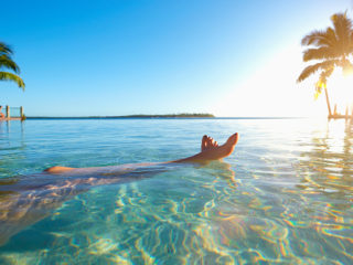 Legs of caucasian girl relaxing in tropical ocean
