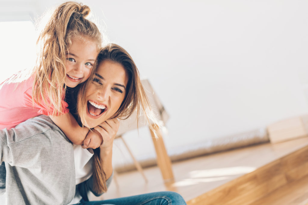 Young woman and small girl having a great time together