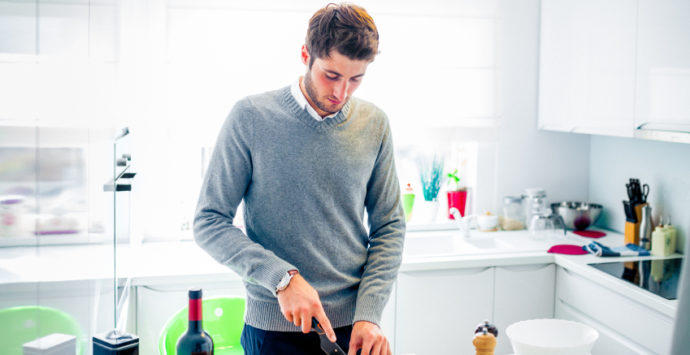 Handsome young man cooking at home cutting vegetables