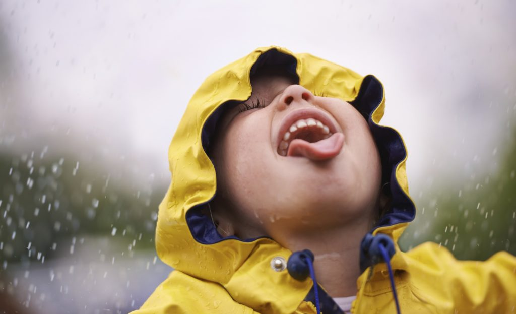 Shot of a young girl playing  in the rain