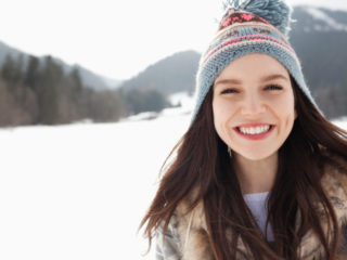 Close up portrait of happy woman wearing knit hat in snowy field