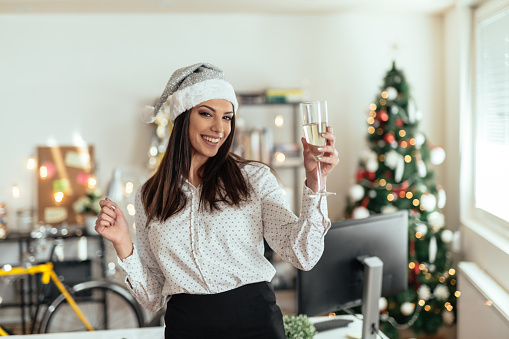 Young businesswoman drinking champagne and celebrating christmas in her office