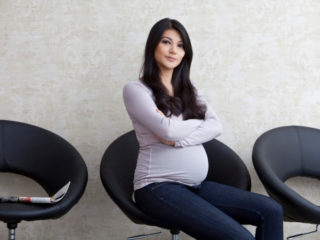 Pregnant woman sitting on chair in waiting area