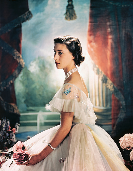 (Original Caption) Princess Margaret Rose of England, is shown here seated and wearing a formal evening dress with sequence butterflies around the shoulder, and holding two pink roses.