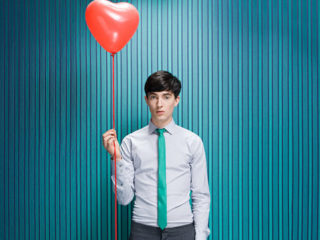 Young man with heart shaped balloon