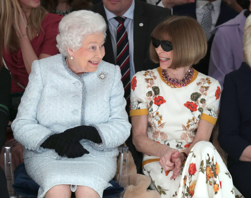 LONDON, ENGLAND - FEBRUARY 20:  Queen Elizabeth II sits next to Anna Wintour as they view Richard Quinn's runway show before presenting him with the inaugural Queen Elizabeth II Award for British Design as she visits London Fashion Week's BFC Show Space on February 20, 2018 in London, United Kingdom. (Photo by Yui Mok - Pool/Getty Images)