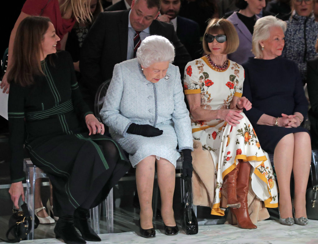 LONDON, ENGLAND - FEBRUARY 20: Queen Elizabeth II sits with Anna Wintour, Caroline Rush (L), chief executive of the British Fashion Council (BFC) and royal dressmaker Angela Kelly (R) as they view Richard Quinn's runway show before presenting him with the inaugural Queen Elizabeth II Award for British Design as she visits London Fashion Week's BFC Show Space on February 20, 2018 in London, United Kingdom. (Photo by Yui Mok - Pool/Getty Images)