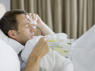 Man sick in bed drinking hot drink
