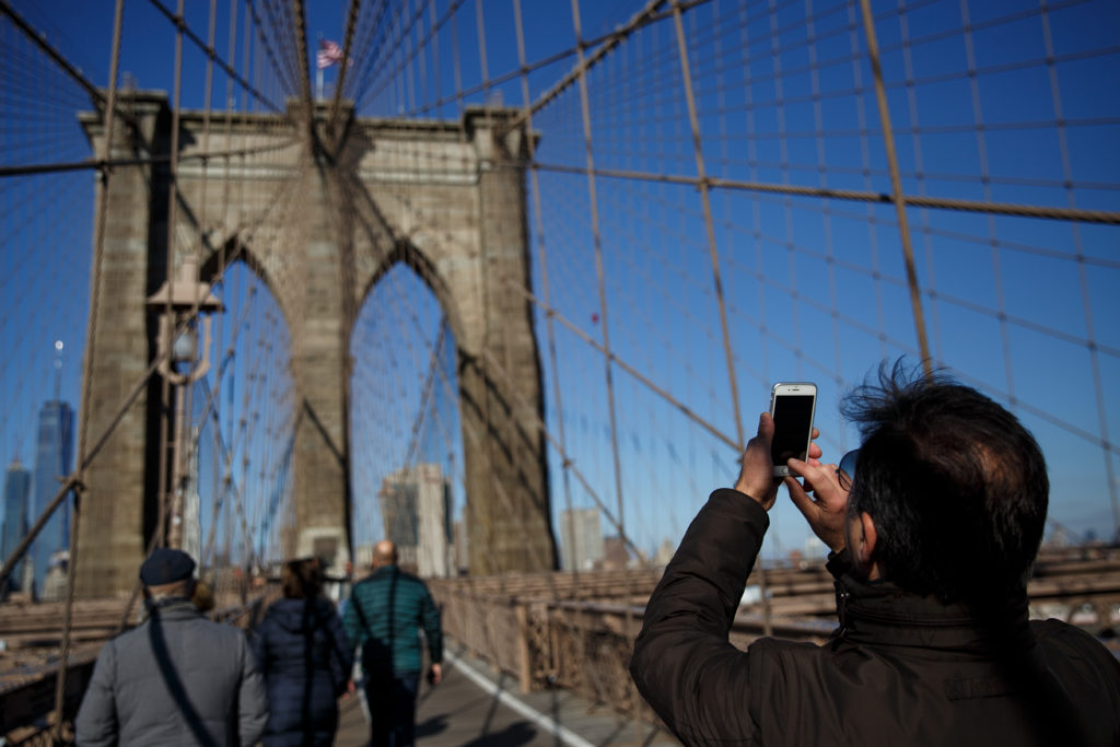 NEW YORK, NY - DECEMBER 01: A man takes a photograph on the Brooklyn Bridge, December 1, 2017 in New York City.  The photo-sharing app Instagram has released data for its most-Instagrammed cities and locations for 2017. New York City is ranked number one, with Moscow and London coming in second and third. Among the most photographed locations in New York City were the Brooklyn Bridge, Times Square and Central Park. (Photo by Drew Angerer/Getty Images)