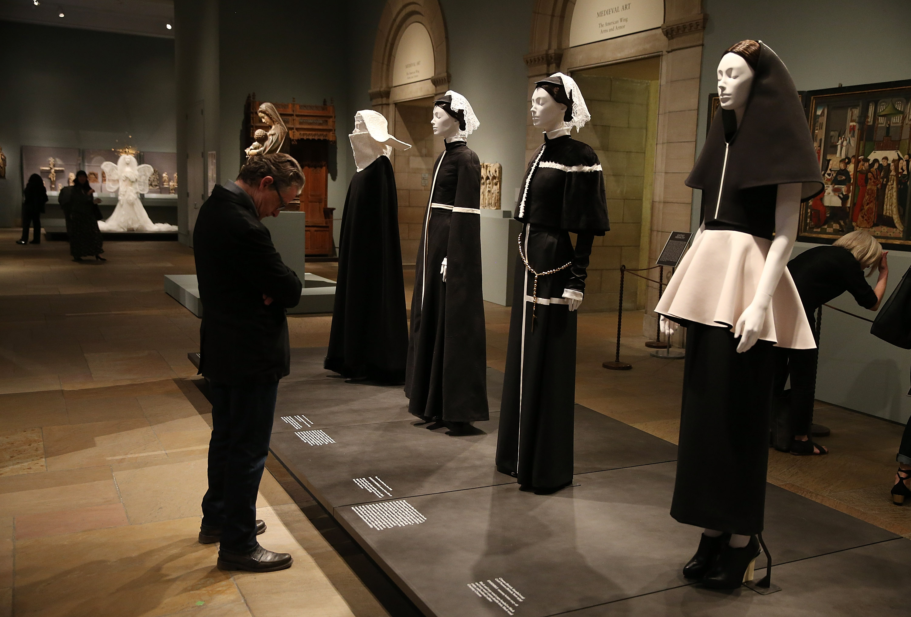 NEW YORK, NY - MAY 07:  A patron looks at fashion on display during the Heavenly Bodies: Fashion & The Catholic Imagination Costume Institute Gala Press Preview at The Metropolitan Museum of Art on May 7, 2018 in New York City.  (Photo by Jemal Countess/Getty Images)