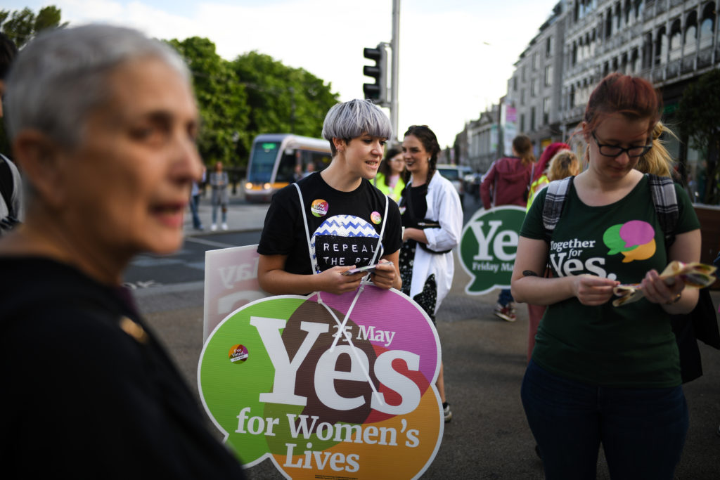 DUBLIN, IRELAND - MAY 25:  Members of the public hold yes placards on Grafton Street as the country heads to  polling stations on May 25, 2018 in Dublin, Ireland. Polling stations are open across the Ireland where voters will decide whether or not to abolish the 8th amendment which makes abortions illegal in the country, unless a mother's life is in danger.  (Photo by Jeff J Mitchell/Getty Images)