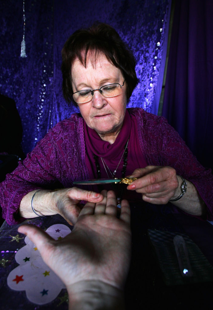 MELBOURNE, AUSTRALIA - SEPTEMBER 21:  A Fortune Teller reads a palm during the Royal Melbourne Show at the Melbourne Showgrounds on September 21, 2004 in Melbourne, Australia. (Photo by Ryan Pierse/Getty Images)