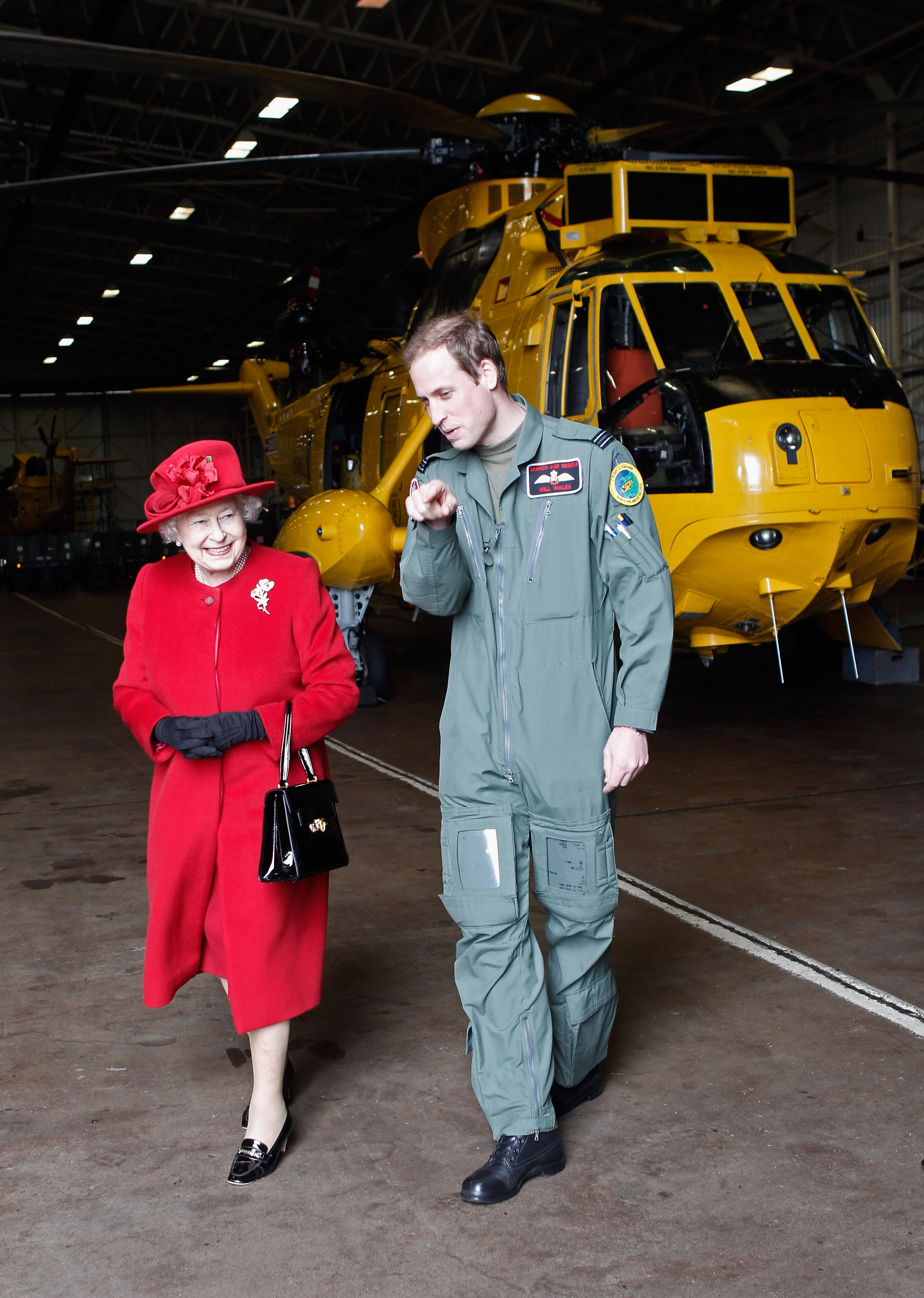 HOLYHEAD, UNITED KINGDOM - APRIL 01: Queen Elizabeth II is escorted by her grandson Prince William during a visit to RAF Valley where Prince William is stationed as a search and rescue helicopter pilot on April 1, 2011 in Holyhead, United Kingdom. The Queen toured the airbase meeting staff and families, watched a fly past and was given a guided tour of a Sea King search and rescue helicopter by Prince William. (Photo by Christopher Furlong-WPA-Pool/Getty Images)