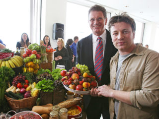 MELBOURNE, AUSTRALIA - MARCH 06:  British Celebrity Chef Jamie Oliver holds a plate full of fresh fruit aloft with Premier of Victoria Ted Baillieu after announcing a partnership to attack state-wide obesity on March 6, 2012 in Melbourne, Australia. The Victorian Government and the Good Foundation will pledge together over AUD5 million to bring Oliver's 'Ministry of Food' to the state to help teach cooking techniques and nutrition to participants and help combat obesity as part of the Victorian Healthy Eating Enterprise.  (Photo by Scott Barbour/Getty Images)