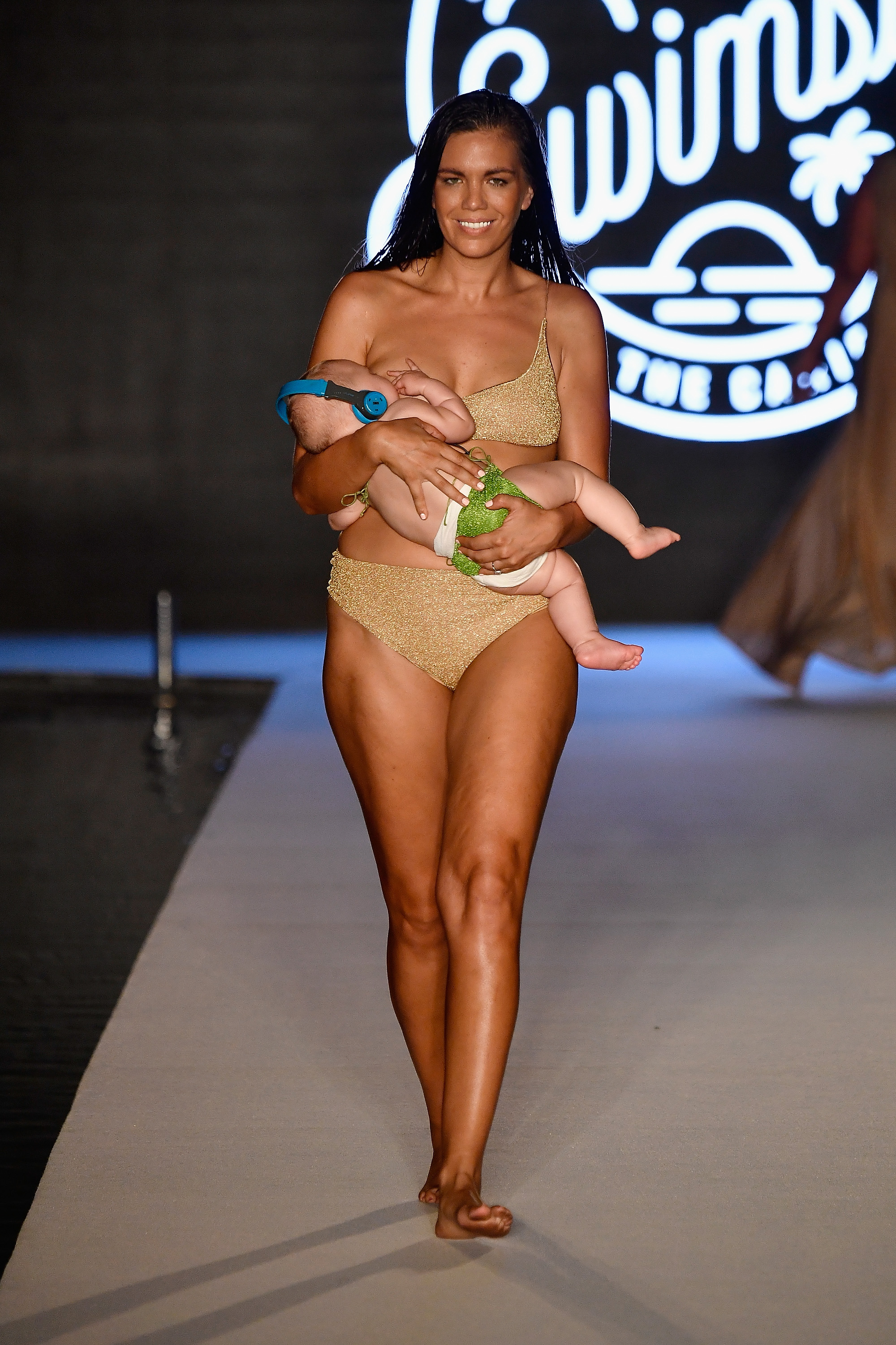MIAMI, FL - JULY 15: A model breastfeeds while walking the runway for the 2018 Sports Illustrated Swimsuit show at PARAISO during Miami Swim Week at The W Hotel South Beach on July 15, 2018 in Miami, Florida. (Photo by Frazer Harrison/Getty Images for Sports Illustrated)
