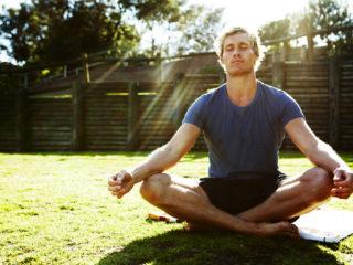 Young man meditating outdoors