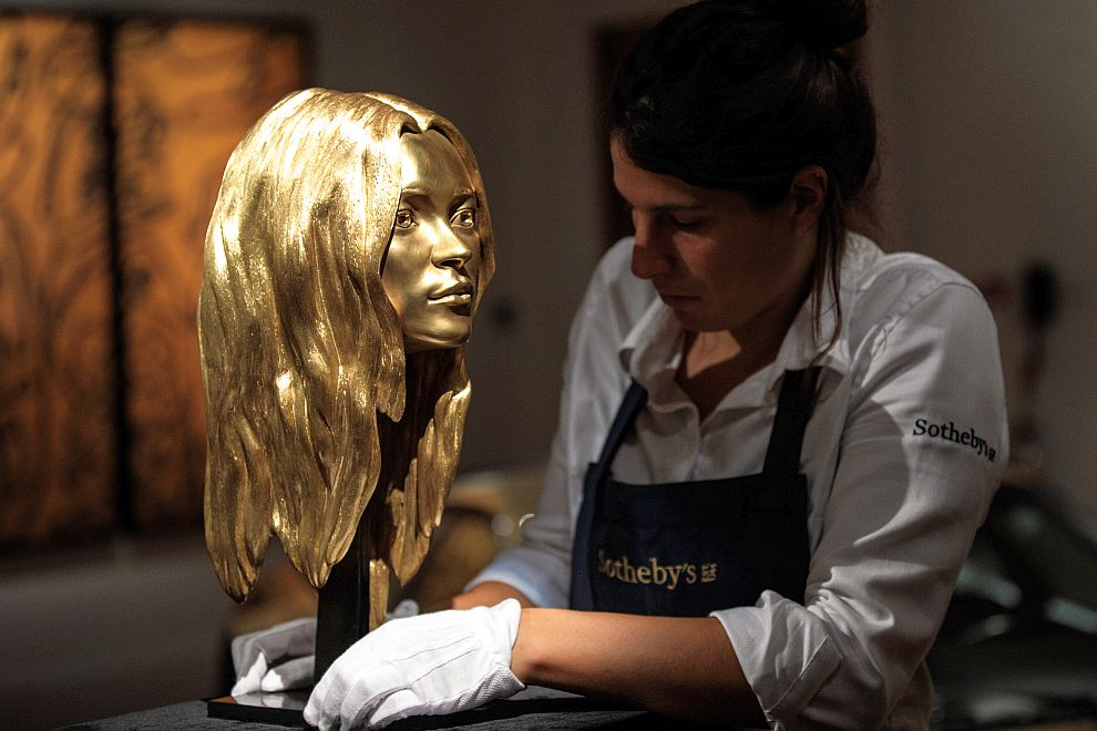 LONDON, ENGLAND - OCTOBER 12: A Sotheby's employee adjusts the 18ct gold 'Head of Kate Moss', 2008 by Marc Quinn during a media preview at Sotheby's auction house for their 'Midas Touch' auction on October 12, 2018 in London, England. The sale, dedicated entirely to gold items, will be held on October 17th, 2018 (Photo by Jack Taylor/Getty Images)