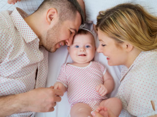 Happy family. Parents with baby on the bed. Closeup.