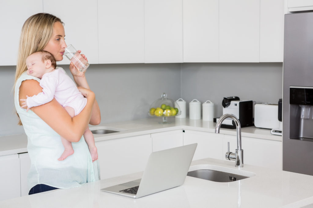Mother drinking water while carrying baby in kitchen at home