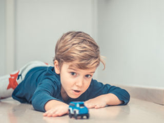 Playful kid having fun with car toy on the floor.