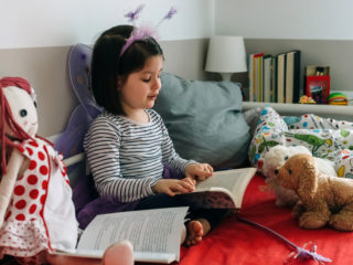 Little girl disguised as a butterfly sitting on the bed reading a book to her toys