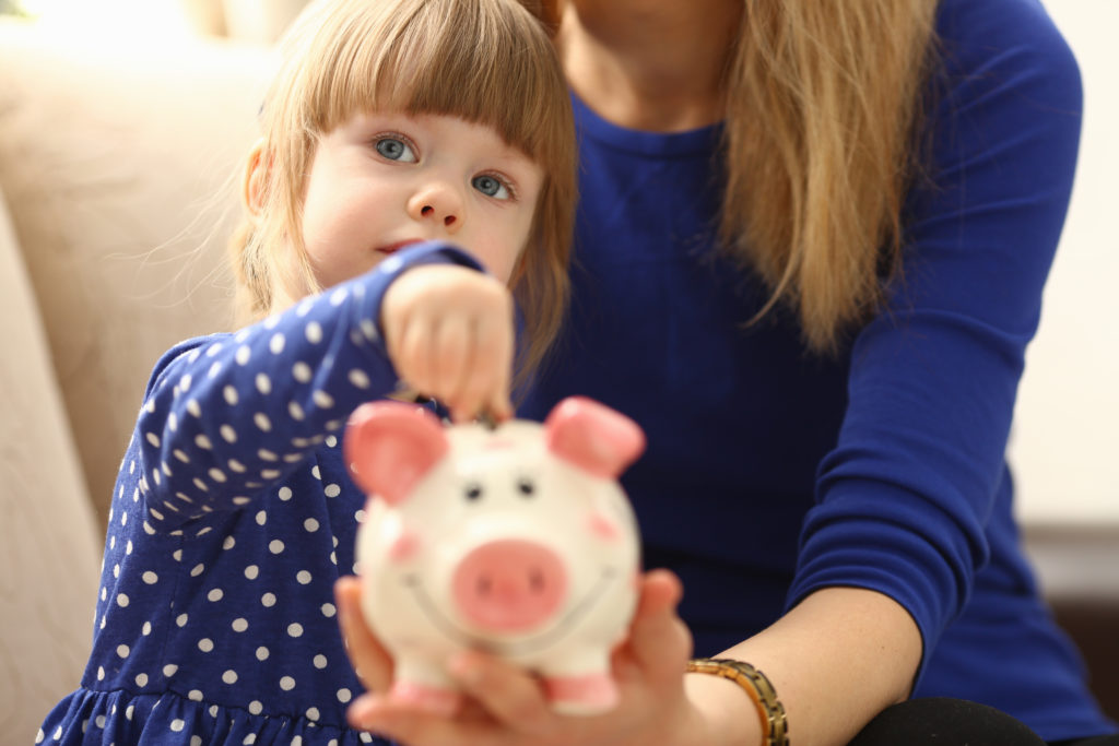 Child little girl arm putting pin money coins into happy pink faced piglet slot portrait. Making effective future needs savings collect dollar gift benefit present home leisure concept