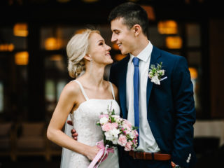 Romantic couple newlyweds, bride and groom holding bouquet of pink and purple flowers and greens with ribbon at the wedding ceremony. Happy and joyful wedding moment.