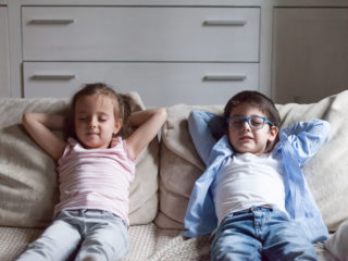 Silent preschool sister and brother sitting on sofa in living room at home. Siblings closing eyes have break breath fresh air putting hands behind heads relaxing thinking. Weekend daydreaming concept