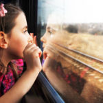 Little girl looking through window. She travels on a train.