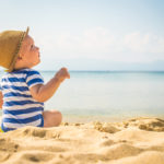 The cute baby boy playing on the beach. Little boy sitting on the sand. Sea and seashore as background with copy space