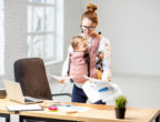 Exhausted businesswoman working with paper documents with her baby son at the office