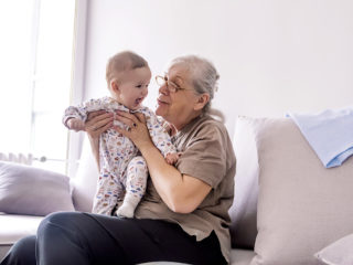 Grandmother holding little grandson in the room at home. Senior woman hold little baby cute smiling. Happy grandmother with her grandchild in home.