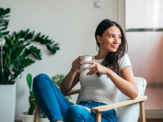 Beautiful young woman drinking tea at home. Looking away.
