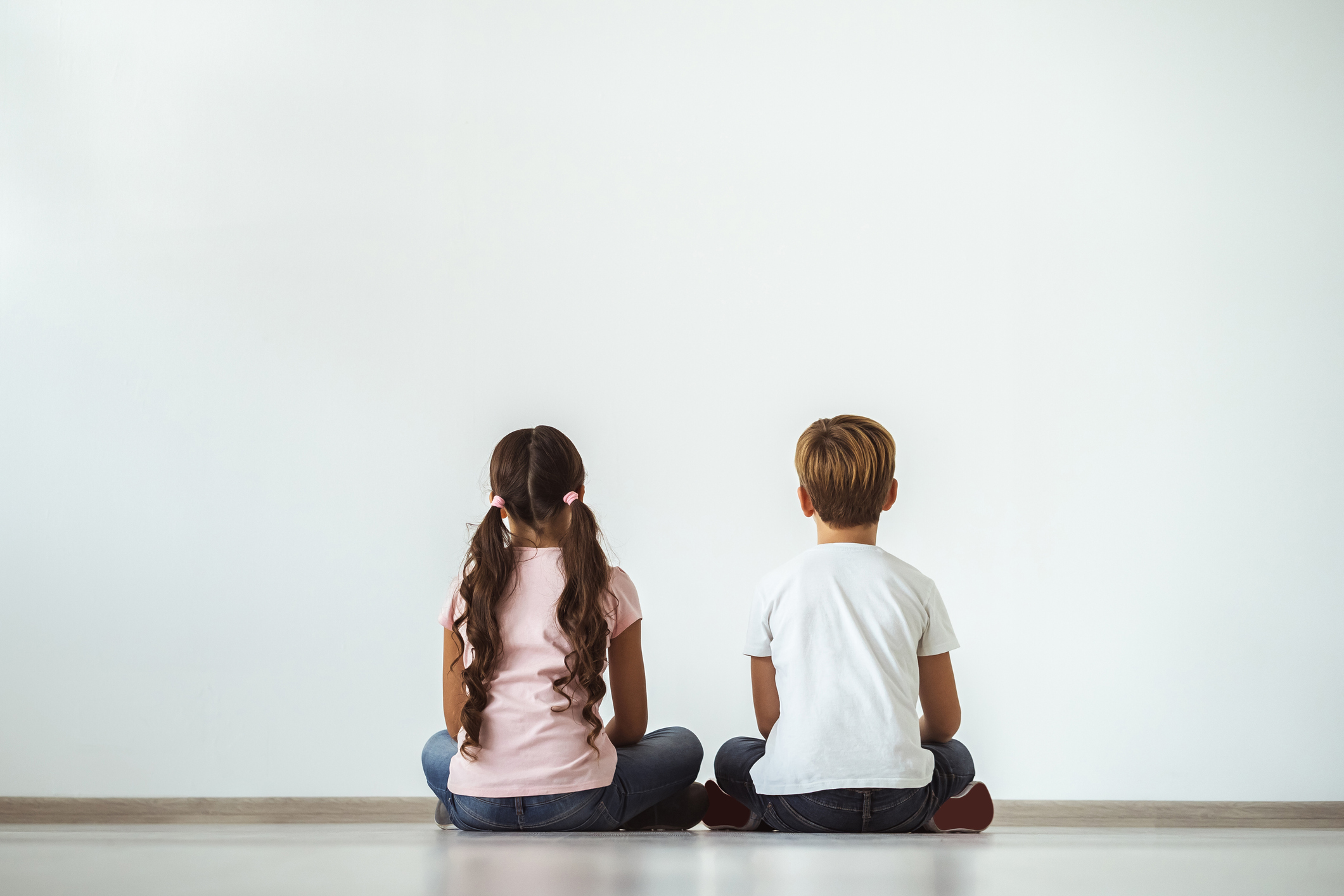 The girl and a boy sitting on the floor on the white wall background