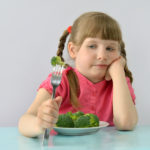 child, kid (little girl) doesn't like broccoli.