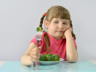 child, kid (little girl) doesn't like broccoli.