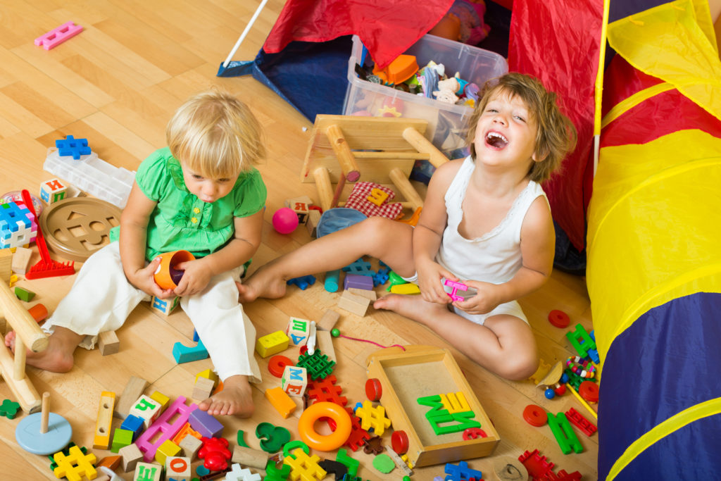 Two happy cute little girls playing with blocks in home interior