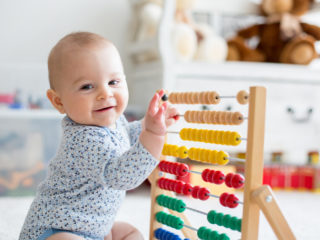 Cute little baby boy, playing with abacus at home, sunny kids room