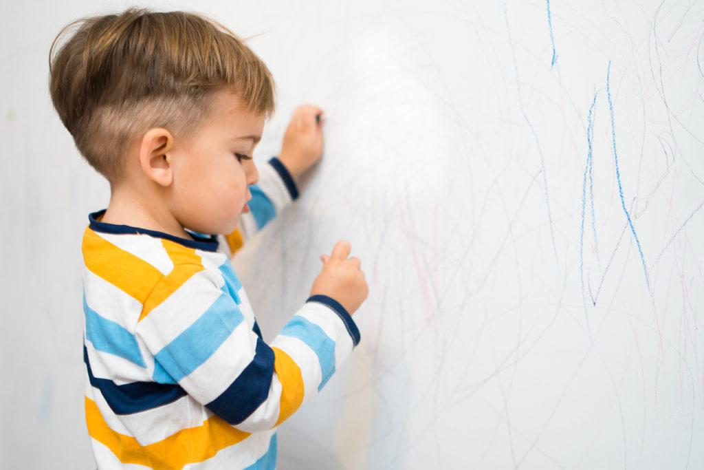 малко момче рисува по стената