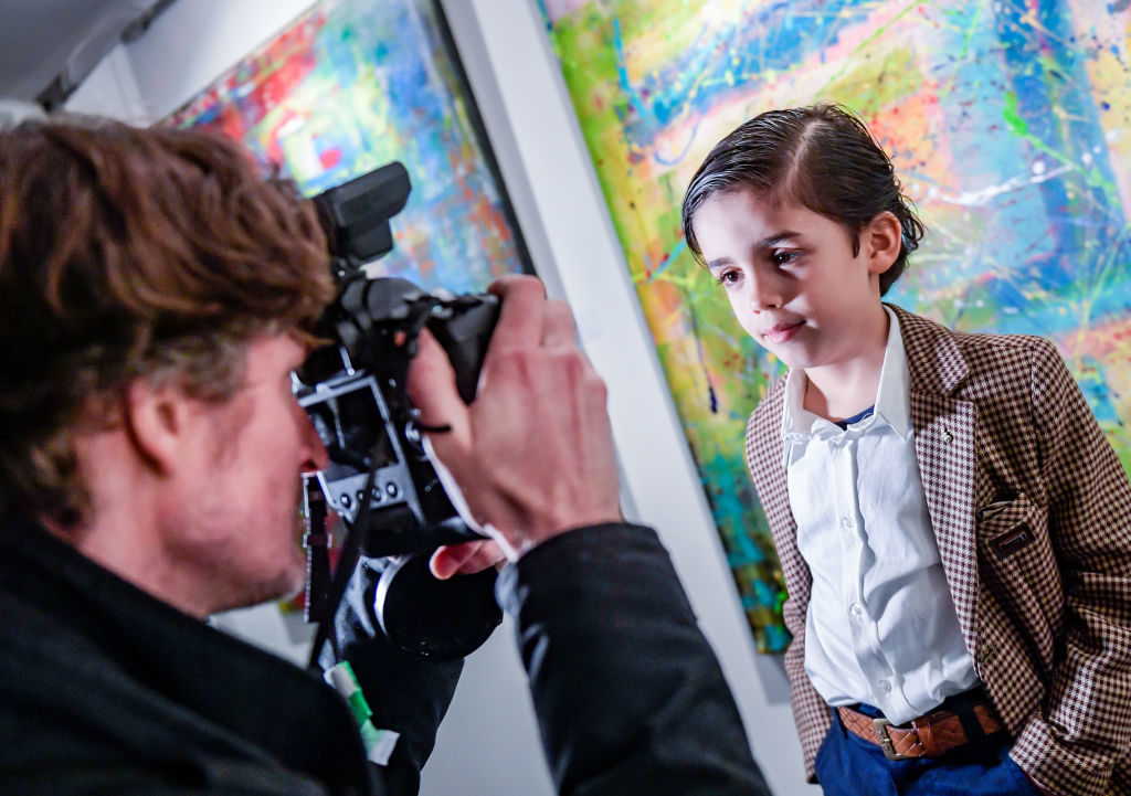 "13 February 2019, Hamburg: Six-year-old Mikail Akar stands in front of his pictures in the gallery ""Nissis Kunstkantine"" in the Hafencity and is photographed. Mikail received a canvas and finger paints as a gift from his parents at the age of four. Since then, the little boy from Cologne has been enthusiastic about painting and constantly tries out new techniques - sometimes with a brush, sometimes with a spatula. After exhibitions in Cologne and Düsseldorf, his colourful works of art can be seen in the Hanseatic city until 28 February 2019. Photo: Axel Heimken/dpa (Photo by Axel Heimken/picture alliance via Getty Images)"