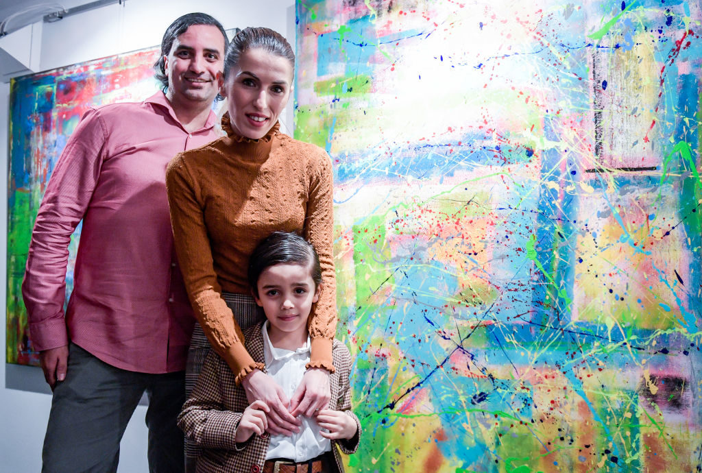 "13 February 2019, Hamburg: Six-year-old Mikail Akar and his parents Kerem (l) and Elvan stand in front of the boy's pictures in the gallery ""Nissis Kunstkantine"" in Hafencity. Mikail received a canvas and finger paints as a gift from his parents at the age of four. Since then, the little boy from Cologne has been enthusiastic about painting and constantly tries out new techniques - sometimes with a brush, sometimes with a spatula. After exhibitions in Cologne and Düsseldorf, his colourful works of art can be seen in the Hanseatic city on 28 February 2019. Photo: Axel Heimken/dpa (Photo by Axel Heimken/picture alliance via Getty Images)"